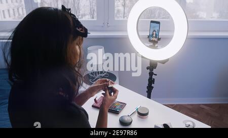 Junge Frau mit schwarzen Haaren Aufnahme Make-up Tutorial. Make-up vor der Kamera auftragen. Hochwertige Fotos