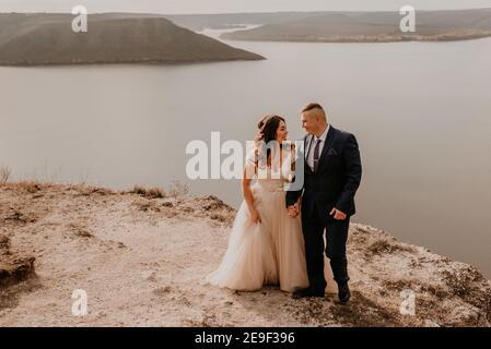 Liebevolles Paar Hochzeit Brautpaar in weißem Kleid und Anzug Spaziergang im Sommer auf dem Berg über dem Fluss. Sonnenuntergang und Sonnenaufgang. Mann und Frau auf Felsen über der Klippe