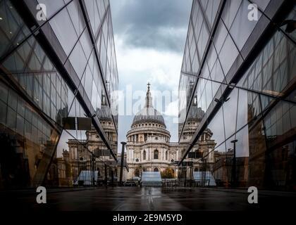 St. Pauls Kathedrale aus dem niedrigen Winkel mit führenden Linien und Spiegelreflexionen im Glas, während sich dramatische Sturmwolken darüber sammeln Modernes Einkaufszentrum