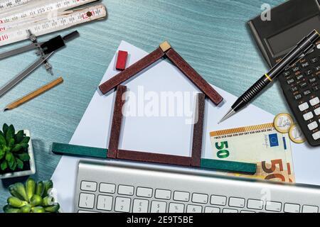 Kleines Holzhaus aus Spielzeugblöcken auf dem Schreibtisch, mit Euro-Währung, Taschenrechner, Klapplineal. Immobilieninvestments Konzept. Stockfoto