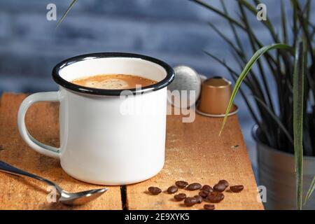 Eine weiße Kaffeetasse mit cremefarbenem Kaffee steht auf einer farbigen hölzernen Oberfläche. Kaffeebohnen sind daneben Stockfoto
