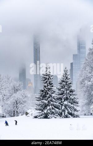 Menschen, die während eines Schneesturms im Central Park einen Schneemann bauen.