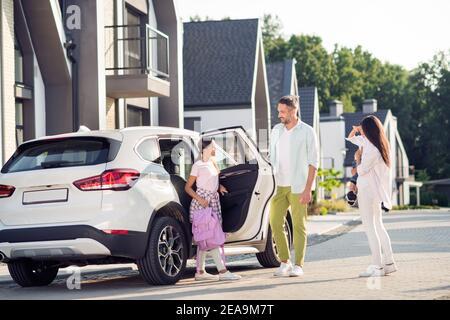 Foto-Porträt der Tochter zur Schule Vater bringt sie Mit dem Auto, während die Mutter auf der Straße über den kleinen Jungen wacht Im Sommer Stockfoto
