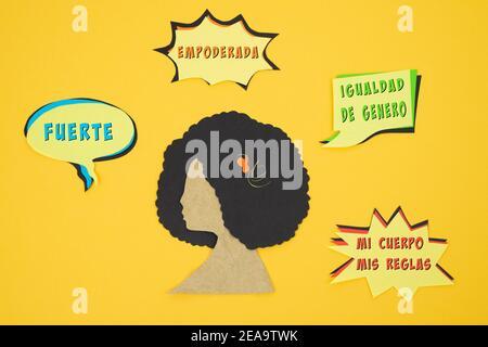Silhouette des Frauenkopfes aus Papier geschnitten mit Botschaften auf Spanisch von weiblicher Ermächtigung auf gelbem Hintergrund. Internationaler Frauentag.