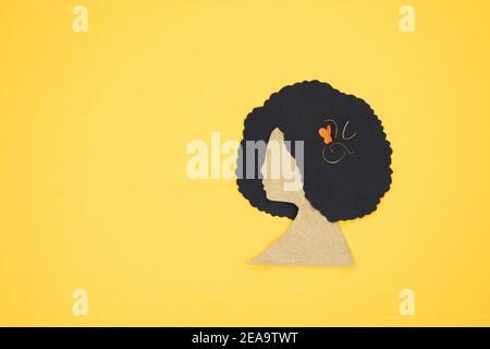Silhouette des Frauenkopfes mit afro Haar in Papier auf gelbem Hintergrund geschnitten. Speicherplatz kopieren.
