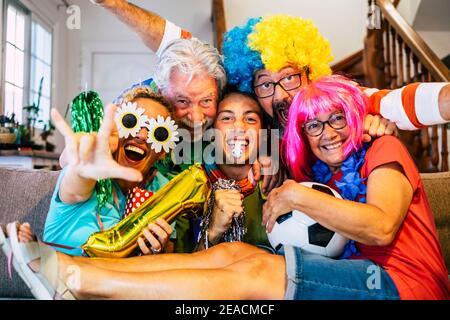Eine Gruppe verrückter und farbiger Fußballfans feiern und jubeln Während des Spiels - gemischte Alter der kaukasischen Menschen Familie Und Freunde genießen Sport-Support-Aktivität zusammen Spaß haben und Gehen Sie für den Teamsieg
