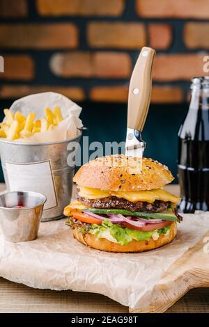 Köstliche saftige Cheeseburger von Brioche Bun. Rindfleisch, Käse, Zwiebeln, Tomaten, Gurken, Salat, Messer, Sauce, Cola und Pommes