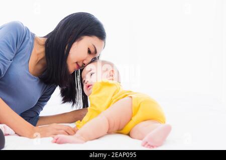 Mutter küsst ihr neugeborenes Baby in einem weißen Bett