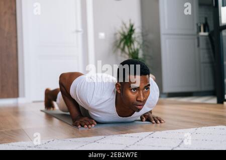 Nahaufnahme eines fokussierten afroamerikanischen Mannes, der auf dem Boden schiebt und wegschaut. Stockfoto