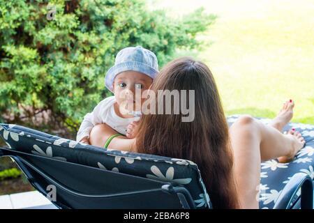 Kind in den Armen der Mutter, neue Mutter ruht mit einem 5 Monate alten Baby auf einem Liegestuhl