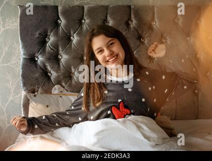 Lächelnde Mädchen im grauen Schlafanzug liegen und rutschen auf der Bett und umarmte eine Katze am Morgen