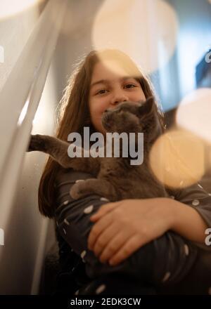 Mädchen in grau Schlafanzug umarmt eine blaue Katze sitzend auf A auf der Treppe