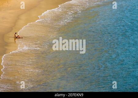 Hochwinkelansicht einer Person, die am Strand sitzt, Plage du Miramar, Biarritz, Frankreich