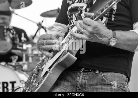 Schwarz-weiß Nahaufnahme von Gitarre spielen mit Trommel Im Hintergrund eingestellt
