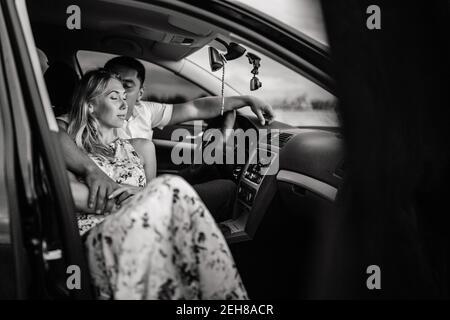 Glückliches Paar sitzt in einem Auto und küsst. Mann küsst Frau