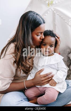 Glücklich jung indisch Mutter spielen küssen gemischt Rennen schwarz Baby Mädchen Tochter. Familie gemischte Rasse Menschen Mutter und Kind zusammen umarmen zu Hause
