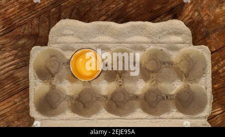 Ein zerbrochenes Ei in einem Pappeifach. Ein halbes Ei mit Eigelb in einer leeren Schachtel auf Holzgrund