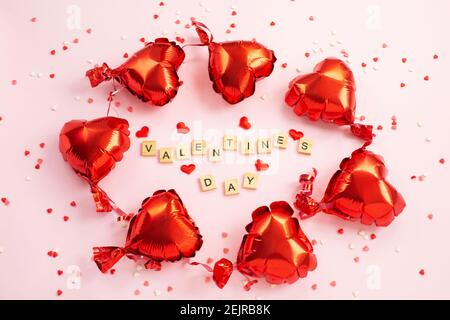 Das Wort Valentinstag aus Buchstaben Blöcke und roten Herzen Foil Ballons um. Romantisches, St. Valentines Day-Konzept. Draufsicht.