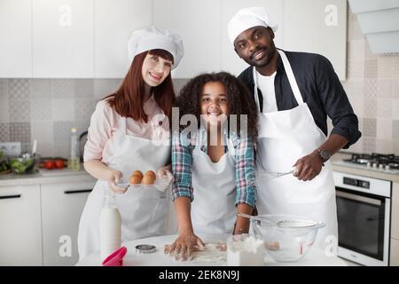 Schöner schwarzer Papa mit Schneebesen in den Händen, attraktive junge kaukasische Mutter mit Eiern und niedliche Teenager gemischte Rasse Tochter Rollen unsere den Teig, machen Stockfoto