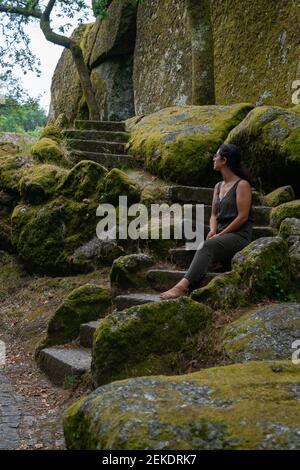 Schöne junge kaukasische Frau sitzt mit einem grünen Kleid auf Eine Treppe im Freien voller Felsen und Bäume Mit Moos