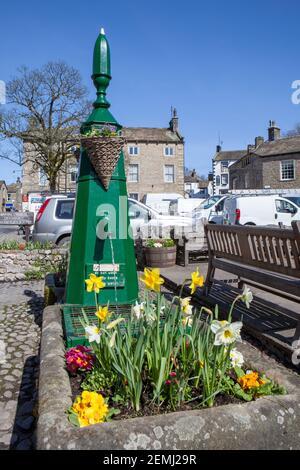 Frühlingsansicht der bemalten Wasserpumpe und -Trog, gefüllt mit Blumen in Grassington, North Yorkshire