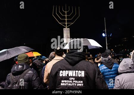 Ein Mitglied von Cop Watch schließt sich den New Yorkern solidarisch an der Beleuchtung der Menorah in der 8th Nacht von Chanukah auf dem Grand Army Plaza in Brooklyn, New York, am 29. Dezember 2019 an. (Foto von Gabriele Holtermann-Gorden/Sipa USA) Stockfoto