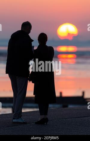 Southend on Sea, Essex, Großbritannien. Februar 2021, 27th. Der warme, sonnige Tag hat mit einem glühenden Sonnenuntergang hinter den Palmen und Besuchern entlang der Küste bei Southend on Sea zu Ende gegangen. Menschen, die auf der Promenade der Western Esplanade spazieren und sitzen, während die Sonne während der COVID 19-Sperre untergeht. Männliches und weibliches Paar, das den Sonnenuntergang beobachtet