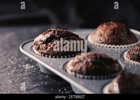 Gerade gebackene Schokoladen-Muffins in Tablett, hausgemachtes Comfort Food Rezept Konzept Stockfoto