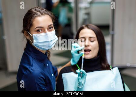 Junge Frau sitzt auf dem Zahnarztstuhl und der Zahnarzt untersucht sorgfältig die Zähne des Patienten. Der Zahnarzt konsultiert einen Patienten, der auf einem Stuhl sitzt
