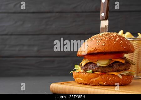 Frischer Burger und Pommes auf schwarzem Holzhintergrund