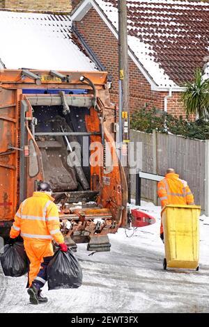Eisschnee & kaltes Winterwetter hohe Sichtbarkeit Müllsammler Arbeiter, die auf der Rückseite mit gelbem Mülltonnen und Müllsäcken umgehen Von Dustcart auf eisiger Straße Großbritannien Stockfoto