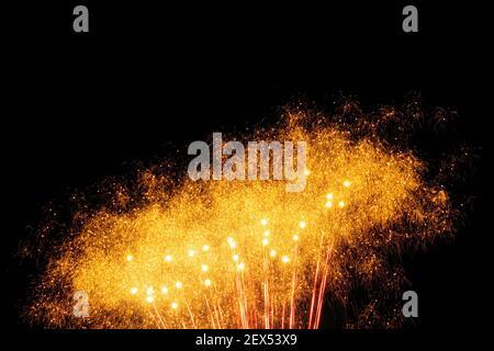 Bild mit einem schwarzen Hintergrund vorbereitet, um Text eines Feuerwerks zu bearbeiten, gebildet von einer Vielzahl von kleinen Lichtpunkten mit mehreren größeren in orange.