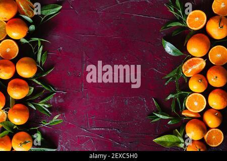 Orangenbaumblätter und frische ganze, halbierte und geviertelte Orangen sind auf einer leuchtend roten Oberfläche mit leerem Kopieplatz in der Mitte angeordnet.