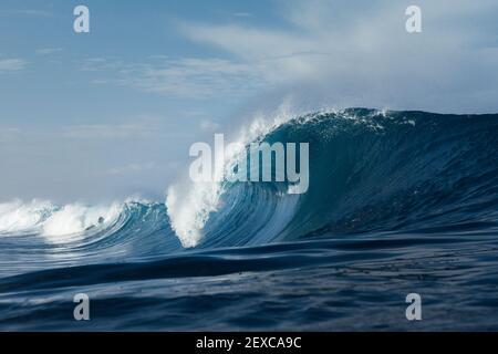 Blaue Welle bricht an einem Strand im Meer