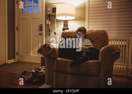 Zwischen Junge arbeiten auf Laptop zu Hause in großen Stuhl