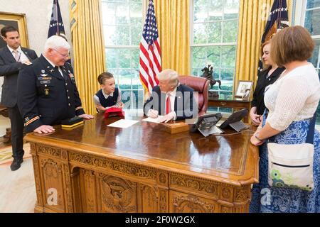 Präsident Donald Trump schreibt eine Ausrede aus der Schulnote für den Empfänger der Ehrenmedaille der pensionierten US-Armee Capt. Gary M. Rose Enkel Christian verließ den Raum während eines Familienbesuchs im Oval Room im Weißen Haus in Washington D.C. im Oktober 23 2017