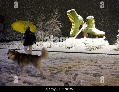 Ein Mann geht mit seinem Hund im Schnee, Sonntag, 19. Februar 2006, außerhalb der Palavela, dem Veranstaltungsort der Figurenkating in Turin, Italien während der Olympischen Winterspiele 2006. (Foto von Andrew P. Scott/Dallas Morning News/KRT) Stockfoto