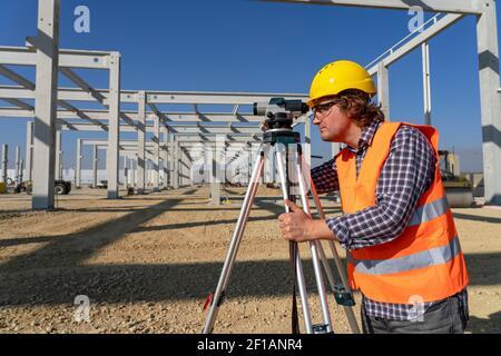 Bauarbeiter in Yellow HardHat vor dem Industriegebäude im Bau. Bauarbeiter mit Tachometer vor Ort im Bau Stockfoto
