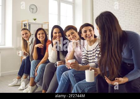 Gruppe von glücklichen jungen Frauen, die Kaffee genießen und zuhören Die Geschichten der anderen Stockfoto