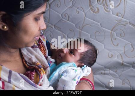 Nahaufnahme Gesicht eines niedlichen neugeborenen Jungen schaut glücklich auf seine Mutter in ihrer Mutter Schoß. Ein Monat altes süßes kleines Kleinkind Kleinkind. Indische Ethnie. F