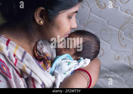 Nahaufnahme Gesicht eines niedlichen neugeborenen Jungen von ihrer Mutter geküsst hält in ihrem Mutterlap. Ein Monat altes süßes kleines Kleinkind Kleinkind. Indische Ethnie.