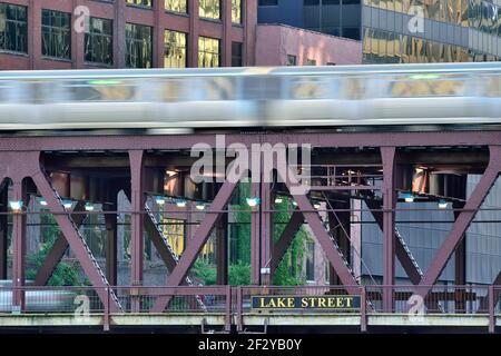 Chicago, Illinois, USA. Ein Chicago CTA Green Line Zug Streifen über den Chicago River zusammen mit Fahrzeugverkehr auf der Lake Street Bridge.