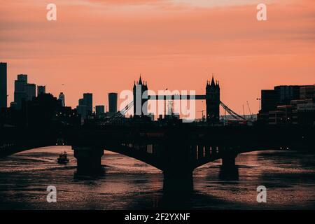 London UK Februar 2021 Spätnachmittag Winter Sonnenuntergang über der Themse, Umriss der Tower Bridge im Hintergrund. Doppeldeckerbusse crossin