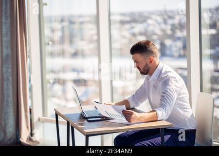 Ein erwachsener erfolgreicher männlicher Geschäftsmann sitzt in seinem Büro mit großen Fenstern und arbeitet an einem Laptop, um an neuen Projekten zu arbeiten.