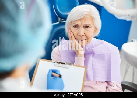 Pensionierte Frau Gefühl Zahnschmerzen und informieren Zahnarzt