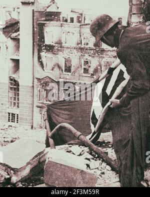 Archivfoto des gefangenen deutschen Soldaten hebt eine Nazi-Flagge aus dem Schutt in Berlin. 1945