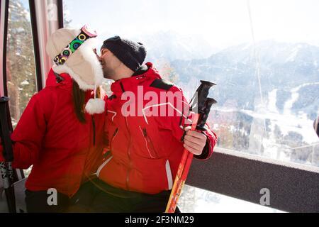 Fröhliche Freunde auf dem Skilift fahren auf verschneiten Berg