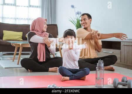 Schöne Familie zu Hause zusammen trainieren