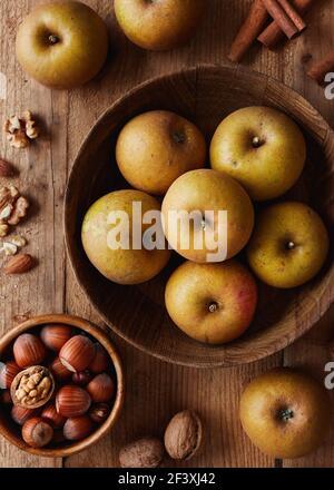 Herbstäpfel mit Nüssen und Zimtstangen auf Tisch, Draufsicht. Erbstück reinette Äpfel.