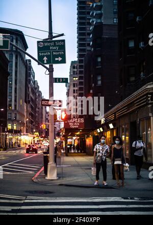 New York City, New York - 18. August 2020: Straßenszene aus Manhattan an einem Sommerabend, an dem Menschen darauf warten, die Straße mit Masken zu überqueren Stockfoto